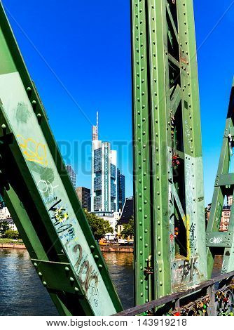 FRANKFURT, GERMANY-AUGUST 17, 2016: The neo-Gothic-style historical bridge Eiserner Steg is a pedestrian bridge over the Main River. The bridge itself is beautiful (over 100 years old) and gives a great view of the city.