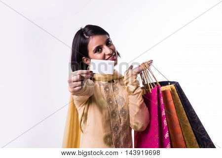 Young smiling indian woman with shopping bags and credit card or blank white card
