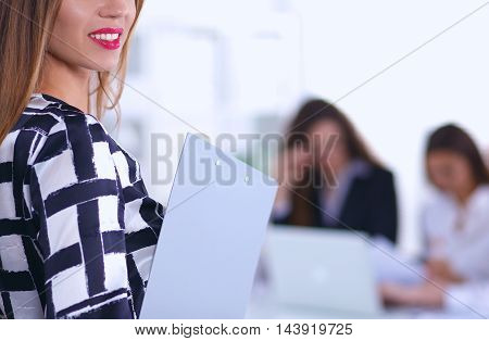 Young woman standing near board with folder, in office