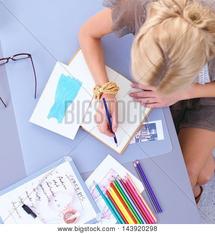 Young female fashion designer working at office desk, drawing while talking on mobile