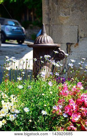 Old water pump with pretty flowers in the foreground Castle Combe Wiltshire England UK Western Europe.