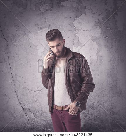 Funny vintage guy with long beard and stylish hair standing in front of urban concrete wall concept
