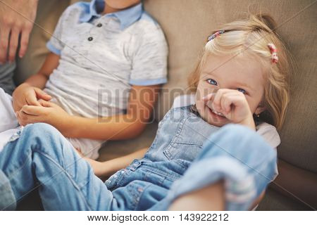 Cute little blonde blue-eyed girl fooling around on couch, smiling and covering face with her hand, dressed in jeans overalls, her brother sitting in background