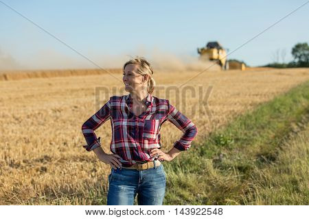happy female farmer in wheat field in summer