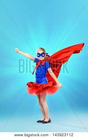 Little girl playing in superhero. Studio shot.