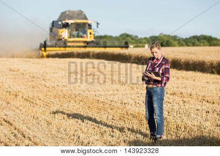 female farmer with combine harvester in wheat field
