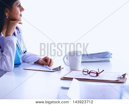 Female doctor sitting on the desk and working