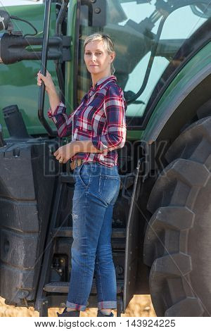 Female farmer and her tractor with sun