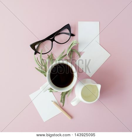 Cup of coffee paper notes pencil green leaves and glasses on pink background. Flat lay top view
