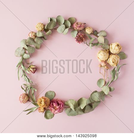 round frame wreath pattern with roses pink flower buds eucalyptus branches and leaves on pink background. flat lay top view