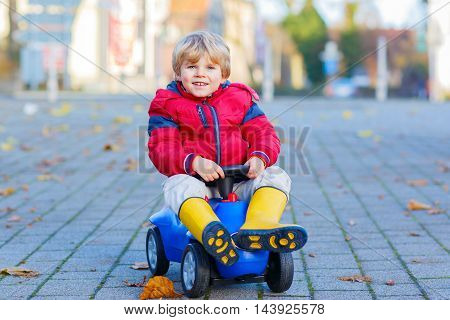Happy cute kid boy in colorful fashion clothes driving toy car. child having fun, outdoors. Active children leisure in autumn