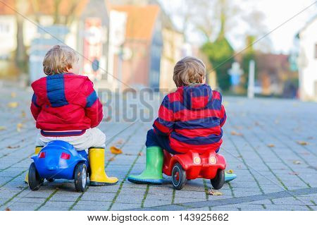 Two little kids boys in colorful clothes and rain boots driving toy cars. Siblings making competition, outdoors. Active leisure for children on spring day