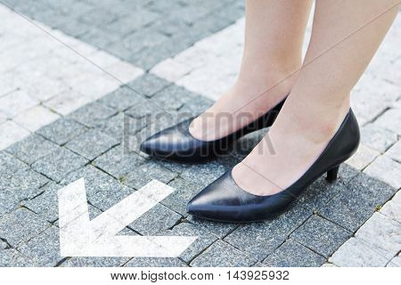 Arrow as concept for success through decision with female shoes on stones