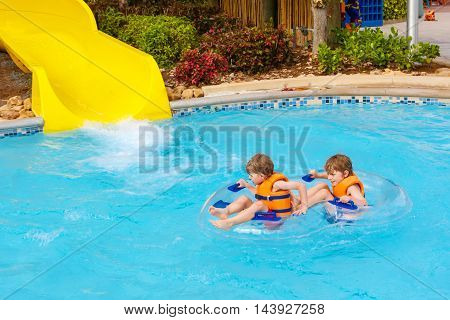 Funny excited children enjoying summer vacation in water park riding on slide with float. Little kids boys having lot of fun together.