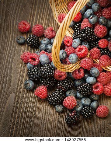 different berries (blueberries raspberries blackberries) in a basket on a wooden table