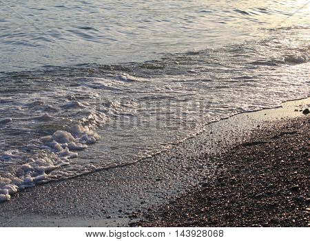 Evening sea beach with shingle in summer at sunset