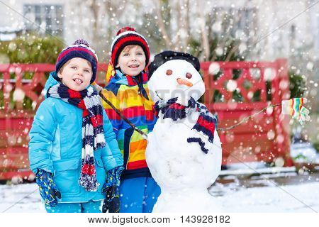 Two little siblings kids boys making a snowman, playing and having fun with snow, outdoors  on cold day. Active leisure with children in winter.