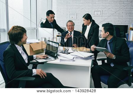 Asian team of lawyers discussing case in office