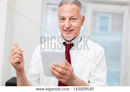 Senior businessman using his tablet