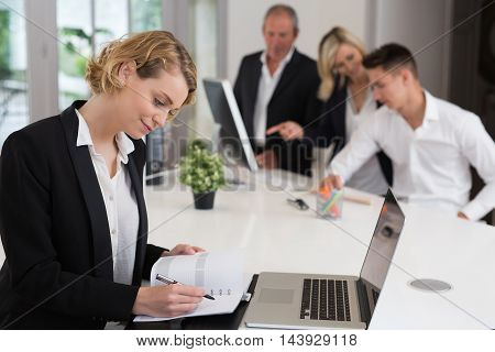 Young woman working in office sitting at desk using laptop