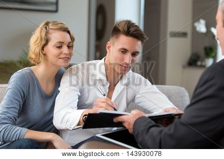 couple in real-estate agency signing with construction planner