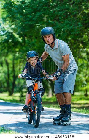 Grandfather Teaching Grandson How To Ride A Bike
