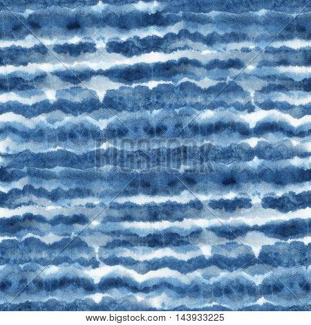 Seamless tie-dye pattern with horizontal stripes of indigo color on white silk. Hand painting fabrics - nodular batik. Shibori dyeing.