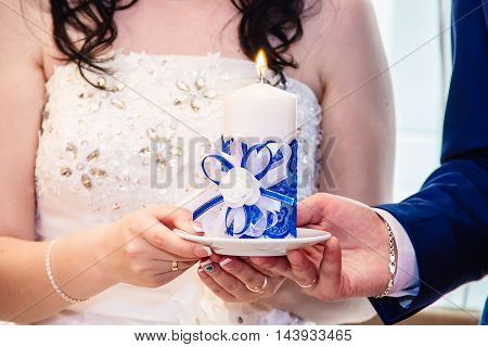 A lit candle in the hands of the newlyweds.