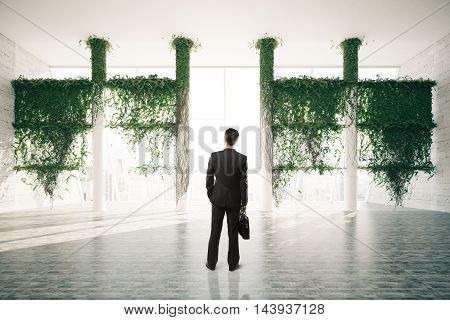 Businessman standing in beautiful bright room interior with plants growing all over columns and city view with sunlight. 3D Rendering