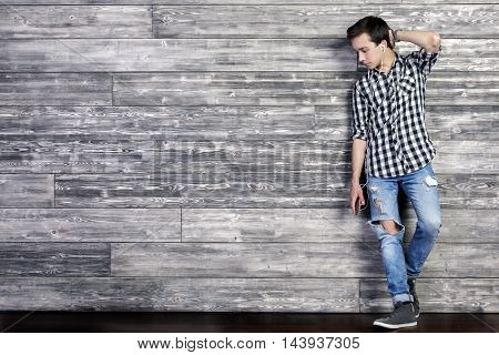 Handsome young guy listening to music on textured dark wooden wall background with copy space. Full length