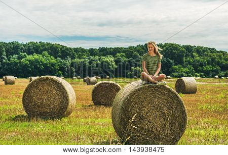 Young blond lady sitting legs crossed on haystack and smiling on sunny summer day, Badasconytomaj, Hungary