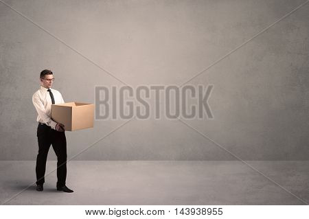 A well dressed young office worker holding an empty paper box with clear concrete wall background concept.