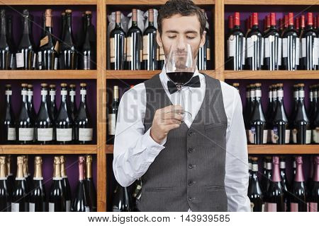 Bartender Smelling Red Wine Against Shelves
