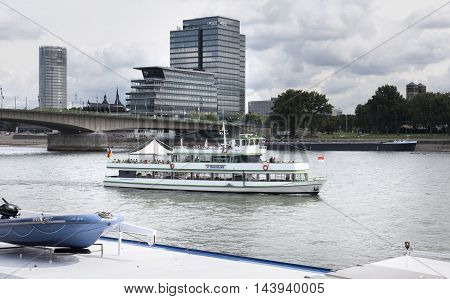 Cologne, Germany - August 20, 2016: Excursion ship Rheinland driving on River Rhine nearby Deutzer Bruecke in Cologne Germany. Some passengers and tourists on the deck