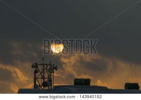 Sun rising behind dark clouds in rainy day