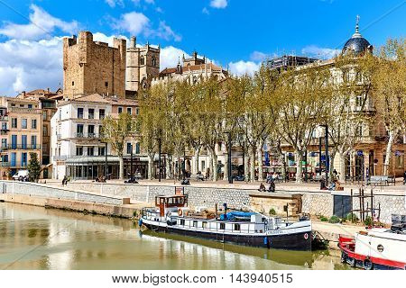 Narbonne France - April 8, 2016: The Canal de la Robine and The Cathedral of Saint-Just and Saint-Pasteur is a former cathedral and national monument of France located in the town of Narbonne. It is dedicated to Saints Justus and Pastor