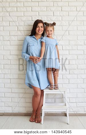 Cute daughter standing on a chair while mother standing on the floor in casual blue-light outfits against a white brick background