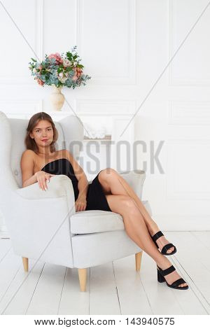A gorgeous woman with red lips and black dress and shoes is relaxing on a cozy white armchair. A charm of her natural beauty makes this photo perfect