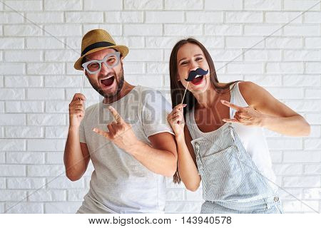 Merry couple holding paper moustache and glasses