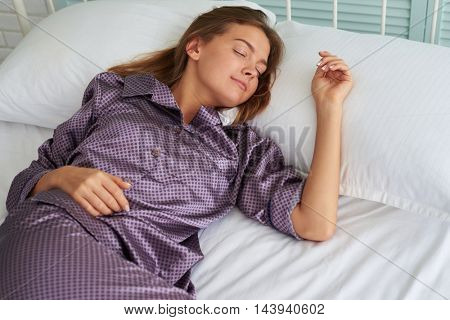 Beautiful woman in satin pajamas is sleeping peacefully on white bedding