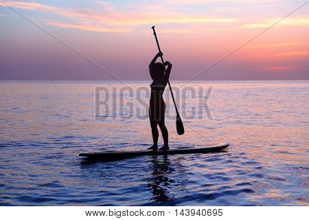 Silhouette of a girl practicing SUP, balancing on paddle board in the sea over beautiful purple sunset, healthy lifestyle and active summer vacation