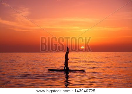 Silhouette of a yoga trainer balancing on the water on the paddle board over beautiful orange sunset background, standing on the head, doing Sirshasana on the beach