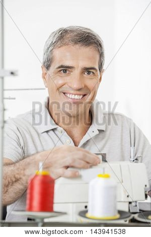Portrait Of Happy Tailor Adjusting Sewing Machine