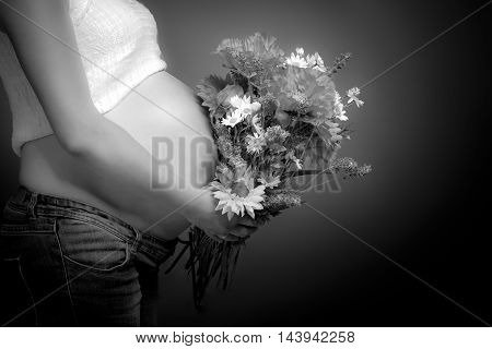 Beautiful pregnant woman with a bouquet of flowers.
