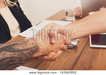 Business handshake at office corporate meeting, contract conclusion and successful agreement concept. Modern hipster businessman and other man's hands meet at wood background.