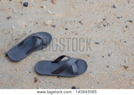 Pair of slippers on a sandy beach.