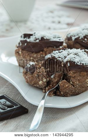 A photo of chocolate cakes on a white plate with a spoon