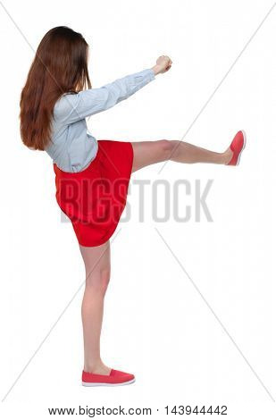 skinny woman funny fights waving his arms and legs. Isolated over white background. Long-haired brunette in red skirt is cancer and has foot.