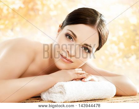 Beautiful, young and healthy woman in spa salon. Massage treatment over yellow autumn background. Traditional medicine and healing concept.