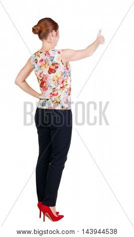 back view of standing young redhead business woman showing thumb up. beautiful businesswoman in black suit gesturing ok sign. Rear view people collection.  backside view of person.  Isolated over